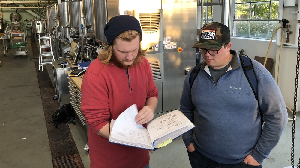 students look through the recipe log book at the fermentation sciences program at Oregon State University (brewery behind them).