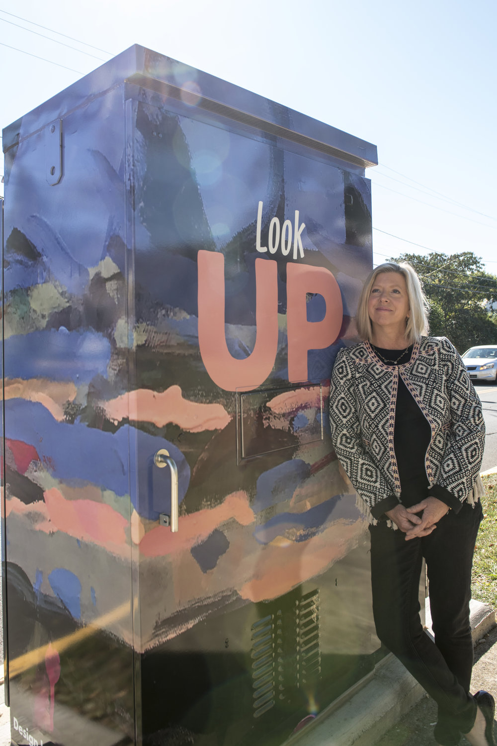 "Sally Veach with traffic control box wrap featuring her painting ""Cloud Five"" in Woodstock Virginia. Photo by HeKyung Parkbarr."