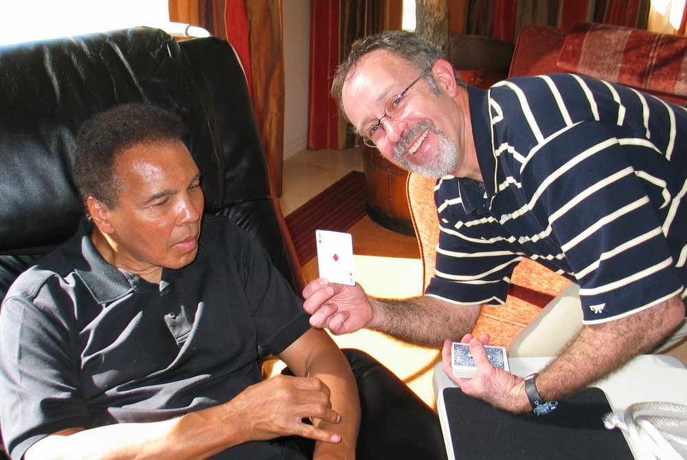 Hondo teaches Muhammad Ali a card trick in his living room in AZ. The Champ loved magic, often pulling coins and silks scarves from behind kids' ears.