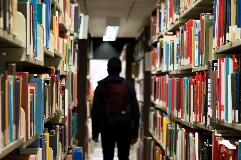 person-wearing-blue-black-jacket-standing-near-gray-bookshelf-203237.jpeg
