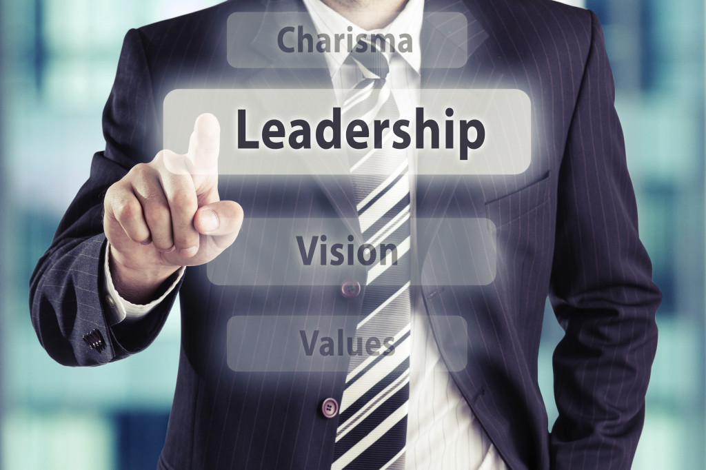 Businessman pressing leadership button at his office. Leadership concept, toned photo.