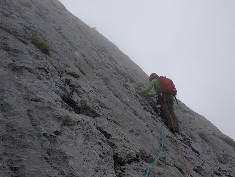 Christine, climbing off into the clouds, stuffing cams into eroded limestone.