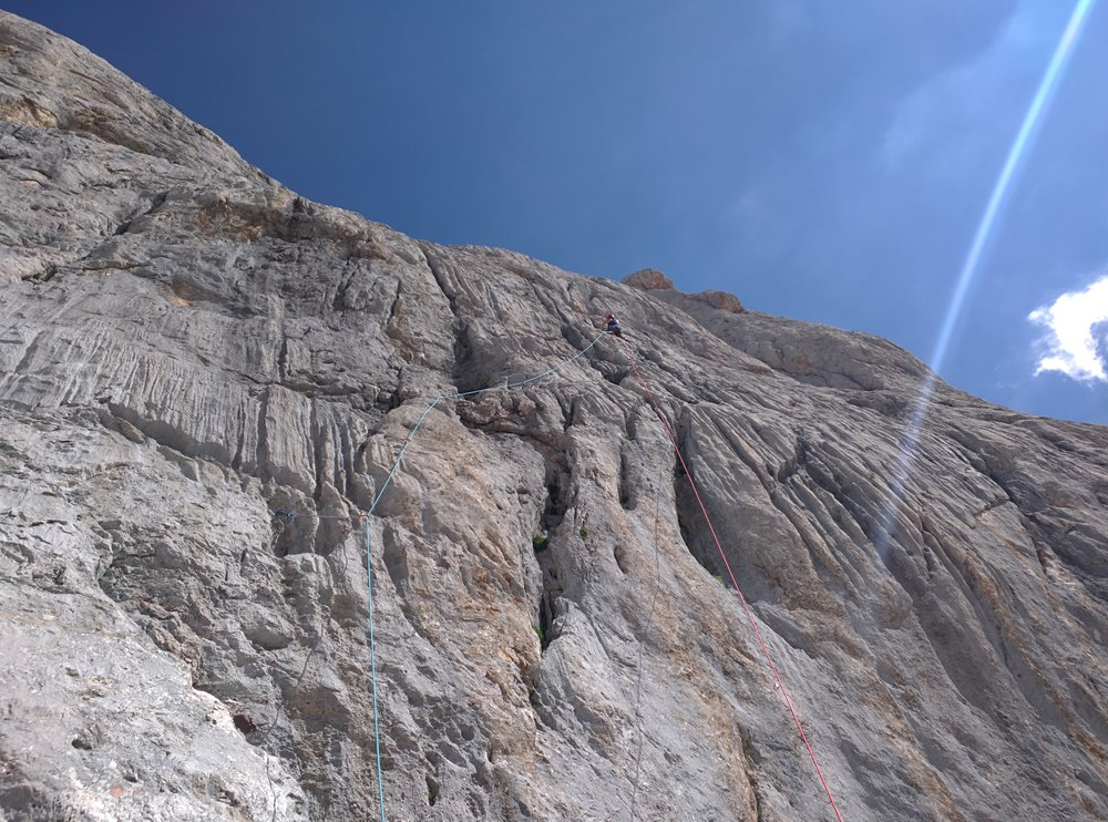 Christine leading a trad line up the super runnelled limestone of the Naranjo de Bulnes in Spain