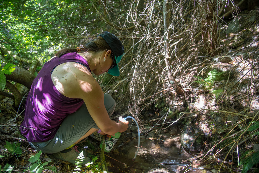 Christine uses Tash's fancy new filter to reload water bottles in from an overgrown ditch beside the road