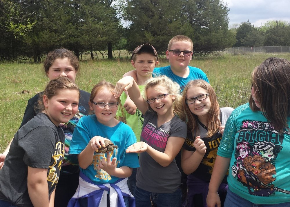 Wapello students explore the Big Sand Mound Preserve on a field trip and show off an ornate box turtle they found.
