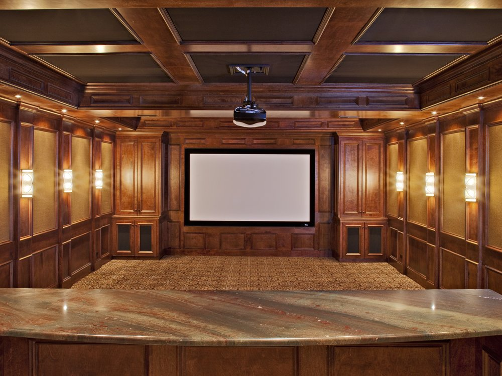 CUSTOM BASEMENT THEATER ROOM WITH WOOD PANELING AND PROJECTOR SCREEN. ELABORATE TRIM WORK AND CUSTOM THEATER SEATS.