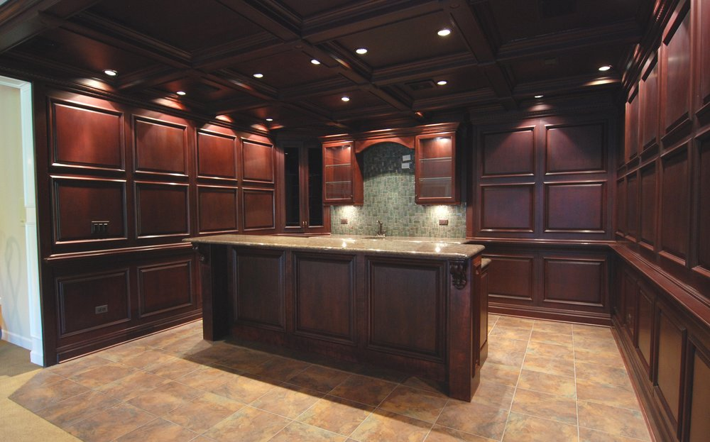 STATELY BASEMENT BAR WITH DEEP CHERRY STAIN AND WOOD PANELING WITH LABRADOR GRANITE IN BARRINGTON IL.