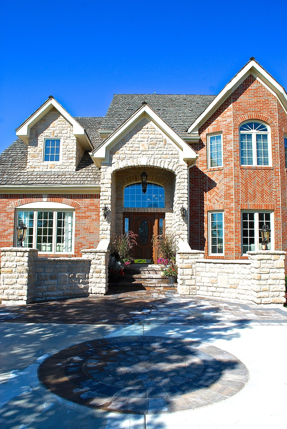 FRONT ENTRY REMODEL WITH NEW CONCRETE DRIVEWAY WITH BRICK PAVER ACCENTS & INLAYS. NEW STONE PILLARS AND STOEN FACADE REMODEL. LIGHTS ON STONE PILLARS