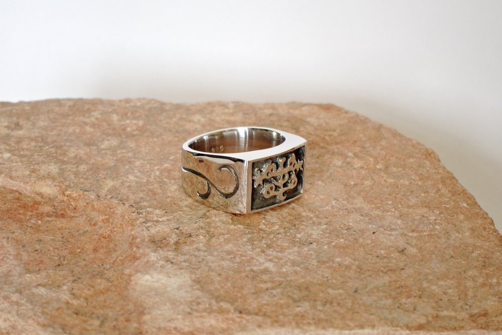 BAHA'I MENS RING | Silver ring with Ringstone relief on an oxidized background, flanked by two floral engraved patterns - inspired by the wrought-iron floral patterns at the Shrine of Baha'u'llah in Akka, Israel.
