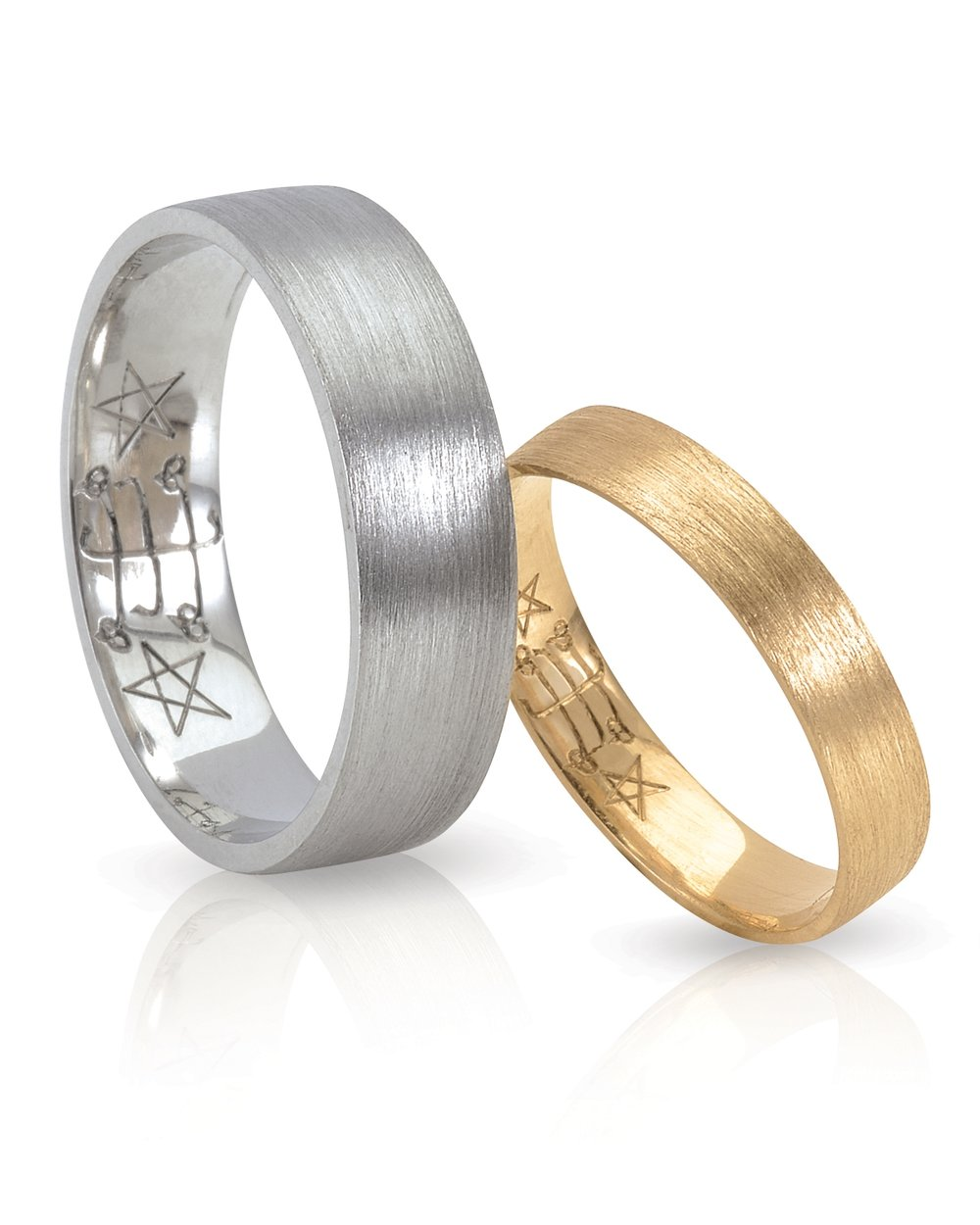 WEDDING BANDS | 18 karat yellow and white gold flat bands with brushed finishes and hand engraved Ringstone Symbol.