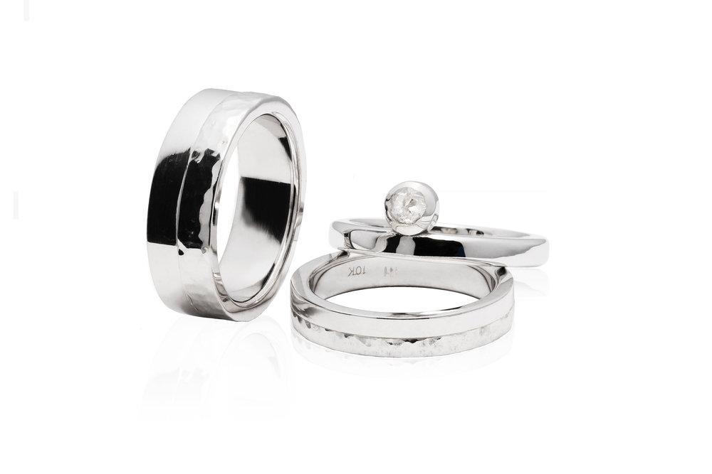 WEDDING SET | 10 karat half-hammered wedding bands and an accompanying 14 karat engagement ring with a bezel set rose-cut salt & pepper 0.21 carat diamond.