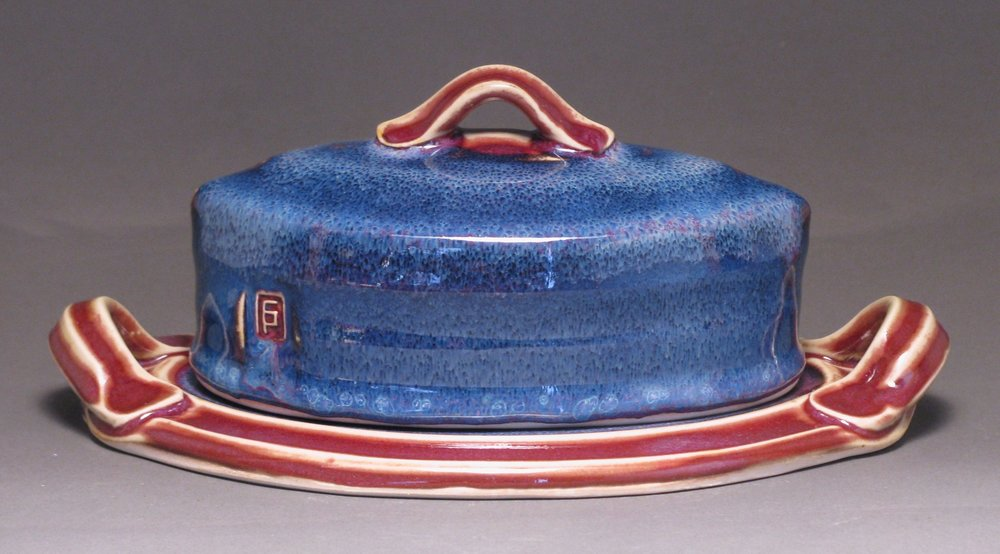 "Oval butter dish  8.5"" long  Glazes: purple haze and copper red"