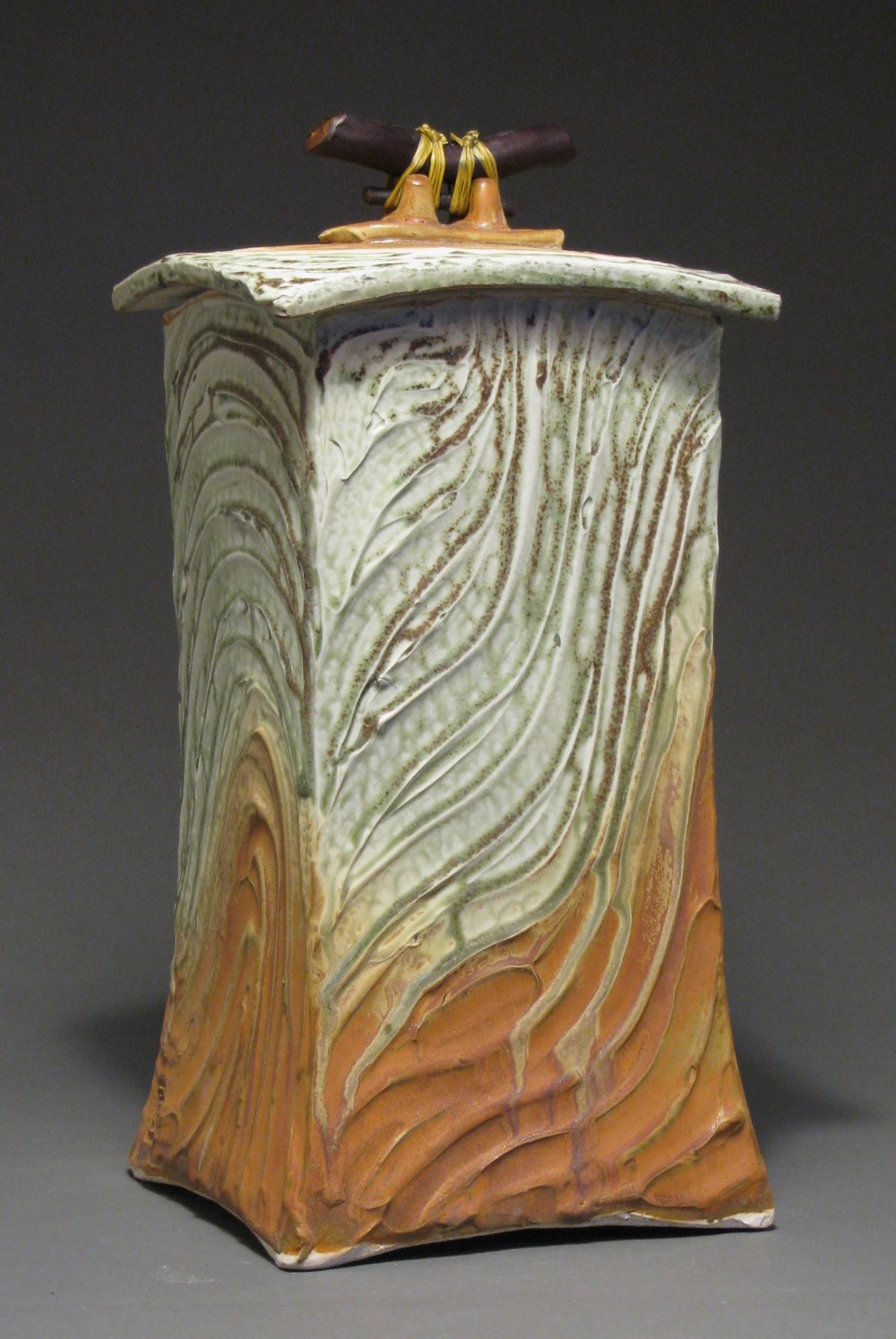 "Lidded box or funerary urn  13 1/4"" tall by 6 1/4"" deep by 6 1/4"" wide  Glazes: green ash and matte rust"
