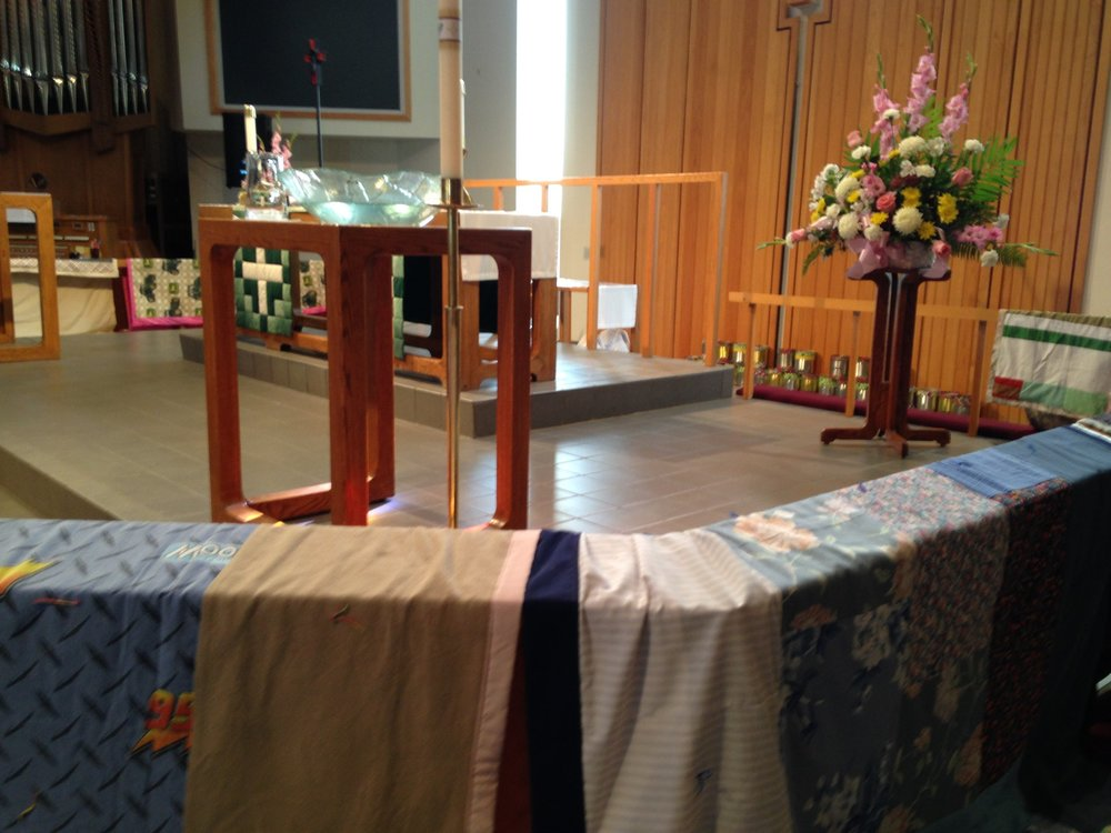 Quilts made for the homeless placed around the Altar Table.