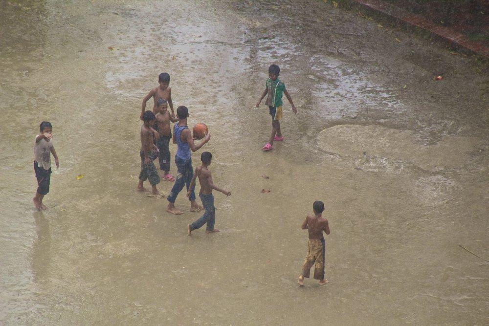 dhaka bangladesh slums children play in monsoon rain.jpg