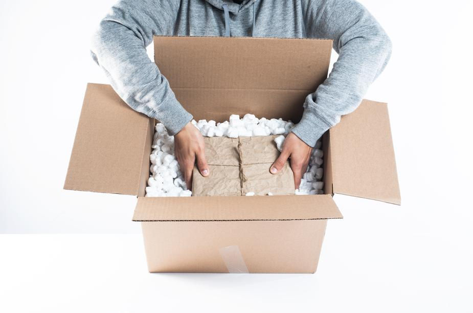 a man carefully packing a box