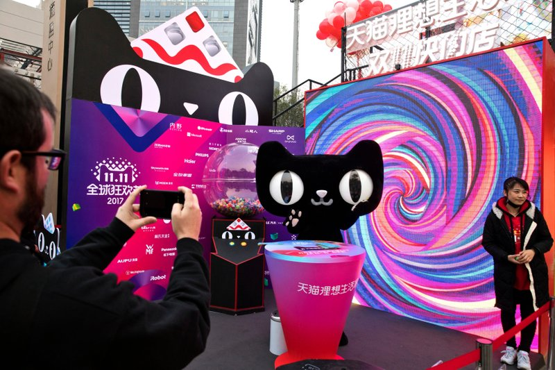 In Nov. 6, 2017, photo, a mascot for Tmall, an online shopping website owned by Alibaba, promotes Singles Day in Beijing, China. (AP Photo/Ng Han Guan, File).