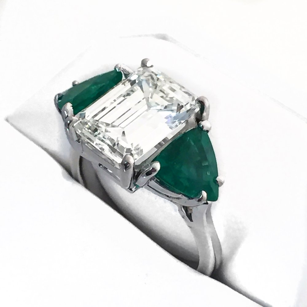 Platinum Fancy Ring with side triangle cut Emeralds.