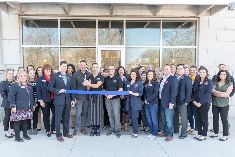 Tip Top Cakes and the Iowa City Area Chamber of Commerce celebrate with a ribbon cutting ceremony.