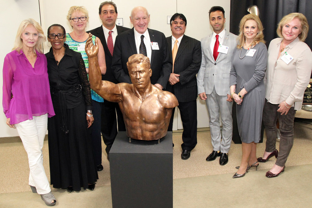 From left are United States Sports Academy's Art Committee members Kay Daughdrill; B.J. Cooper; and chair Nancy Raia; Babak Takhti, son of the late Jahan Pahlavan Takhti; Academy Founding President and committee member Dr. Thomas P. Rosandich; Ebrahim Maghsoud, NAIFS President and President of the Hafez Corp. in Mobile; Vahid Abideh, NAIFS Founder and CEO and Secretary General of Iran's Young Journalists Society; committee member emerita and Academy Trustee Susan McCollough; and committee member B'Beth Weldon with sculpture of legendary Iranian wrestler Jahan Pahlavan Takhti presented to the American Sport Art Museum & Archives (ASAMA) by the North American Iranian Friendship Society (NAIFS).  USSA.EDU, ASAMA.ORG