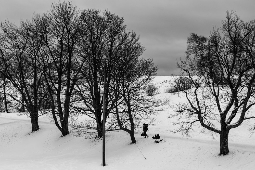 A man walking with his children, who are sitting on sledge.