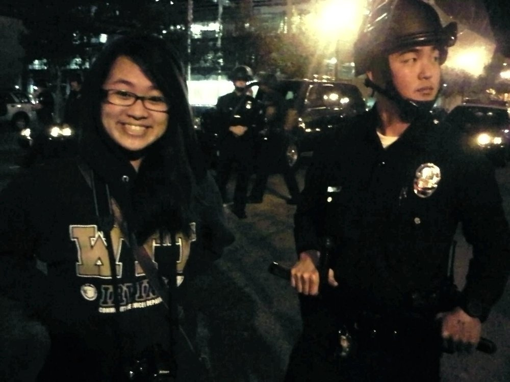 AGE 16: With a Korean policeman in riot gear at Occupy LA