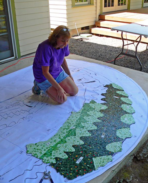 """Here I am """"dry-fitting"""" the sections on a template out on the patio. The whole mosaic will gradually be assembled out here."""