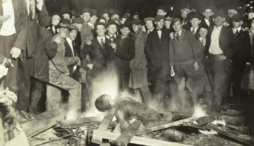 The attackers posed for pictures in front of Will Brown's body.  Notice a young boy to the right looking on and men not ashamed to show their faces in front of the burning body.