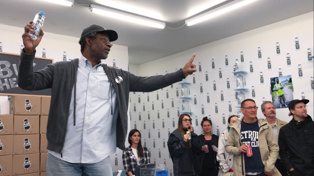 Pope.L auctions a bottle of Flint Water signed by the artist during the opening of Flint Water, September 7, 2017 at What Pipeline, Detroit. Courtesy the Artist and What Pipeline.© Pope.L