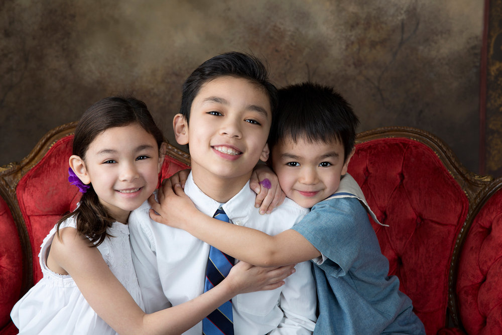 Siblings during a family photo session sitting on an antique red couch.