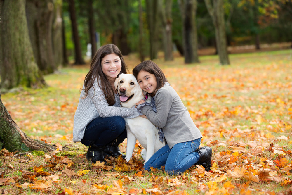 Sisters hugging their Labrador at a photoshoot in Loyd Neck NY