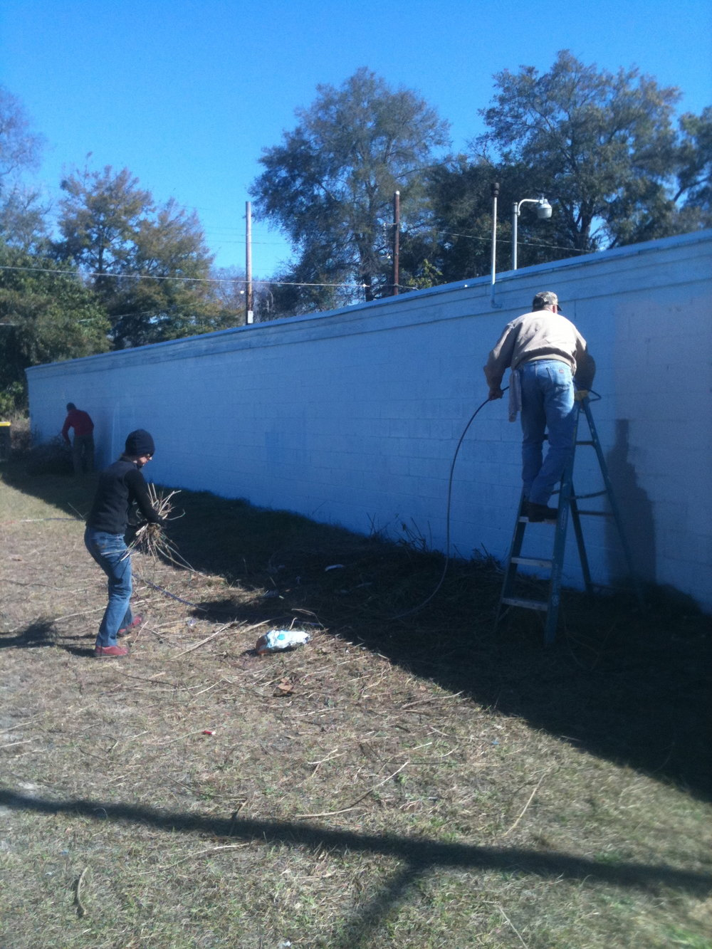 Katherine Sandoz and her husband Dan Bucey prepping the wall and work area.