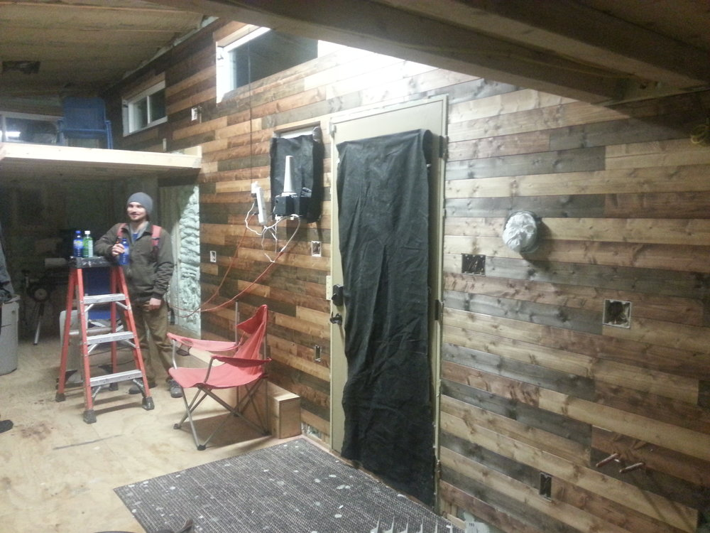 Instead of staining and covering up that wonderful cedar smell I used knotty pine siding.  It was much cheaper and didnt smell nearly as nice.  Simply separated the wood into three piles and went to town with three different colors of stain.  Ventilation is a good thing, if you don't like getting crazy high on stain fumes....  Love this wall, its going to be hard to hang any kind of art on it.