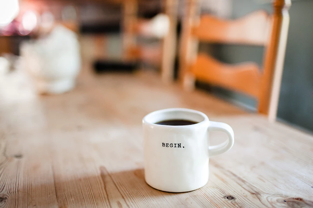 """white mug stamped with the word """"begin"""" on wooden table"""