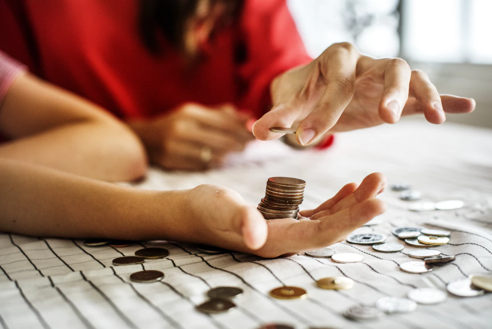 coins being stacked in person's hand and spread out on tablecloth