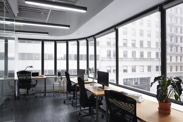 large coworking space with desks and chairs situated in front of large windows