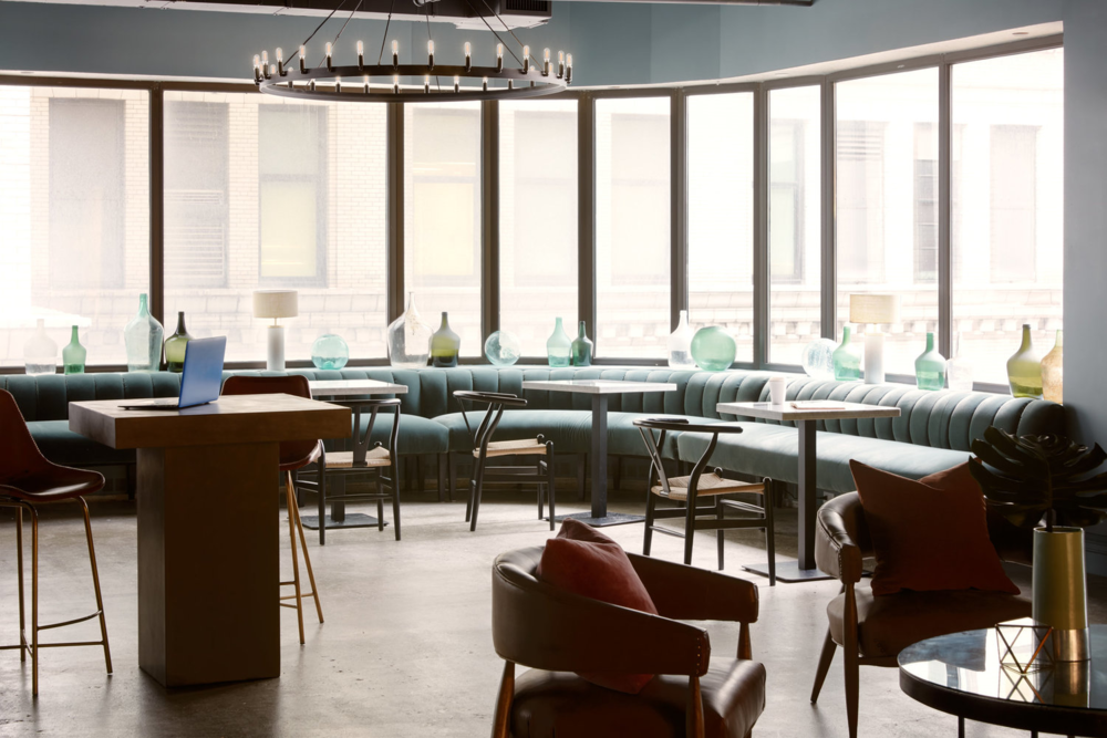 shared office space with large windows, wrap around seating and desks