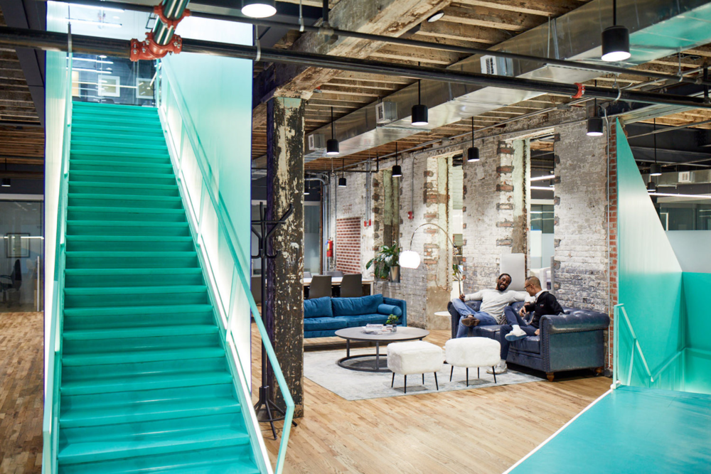 bright and modern coworking space with large staircase and sofas