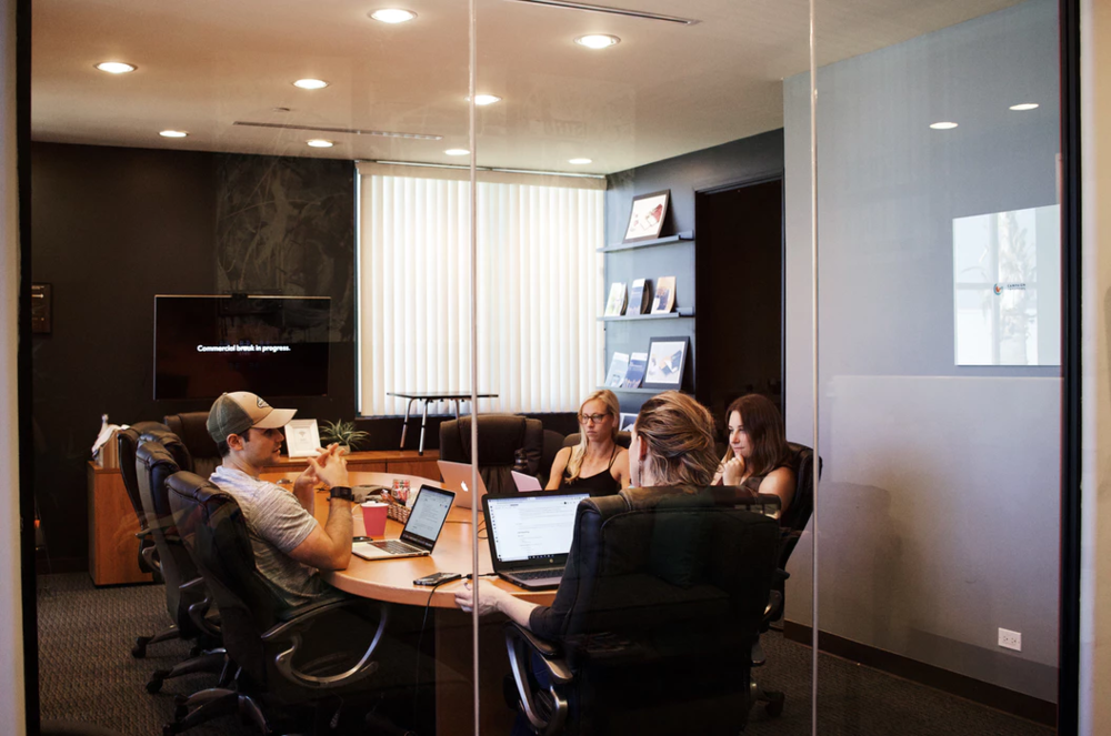 group of coworkers discussing upcoming hiring process around a conference table