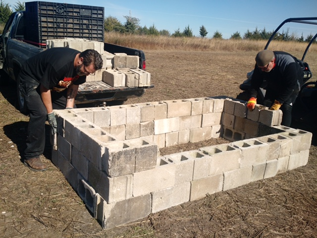 It takes a lot of work to build a giant roasting pit. Chef Josh and Don put blocks into place for the big event.