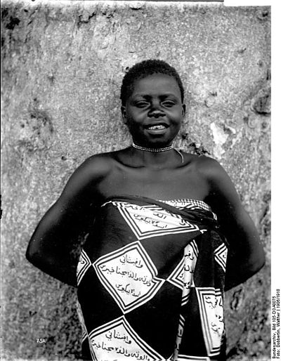 In the 1900s, this Tanzanian girl is wearing a fabric with Swahili Arabic text.