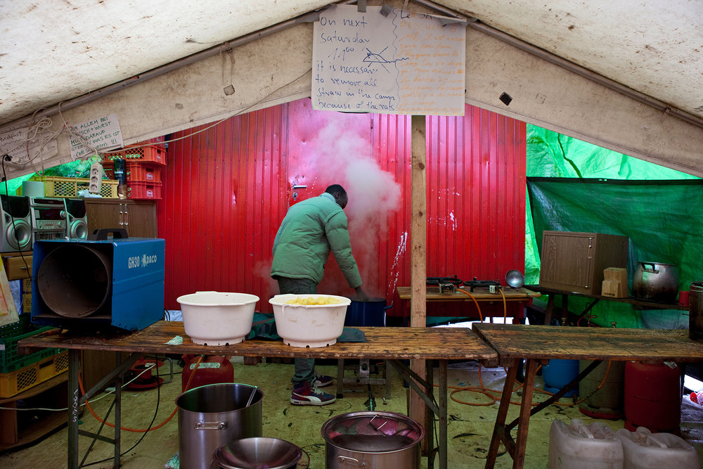 The kitchens of the makeshift refugee camp at Oranienplatz. The tents were put up over wooden crates that were laid down on the ground first. Rats began nesting under the wooden crates and feasting on the garbage, 2013.