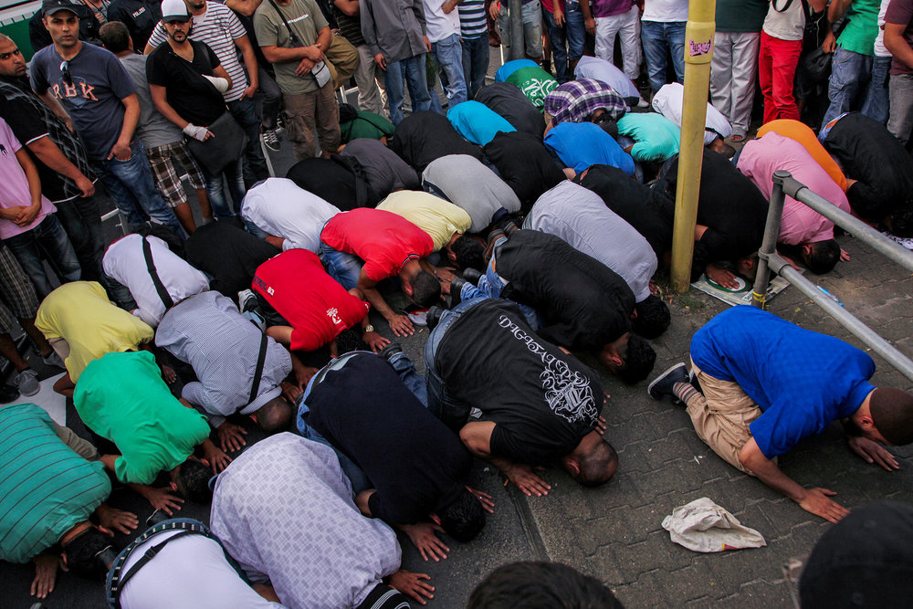 "A group of young Muslim men pray together on the streets of Neukölln. A mark of solidarity and protest towards the ""Pro Deutschland"" group and their ""anti-Islamisation of Europe"" demonstration that took place at several location in Berlin that day, 2012."