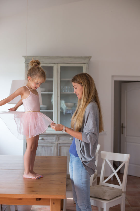 A Mother Dressing Her Daughter Of Ballerina