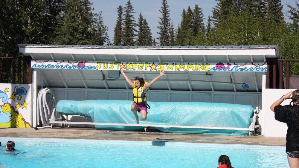 Summer camper jumping into the pool