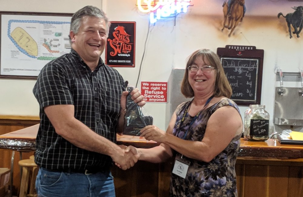Ray Shirts, Vallivue FFA Advisor, accepts the award for the 'Outstanding Agricultural Program' from Past IATA President and Past Homedale FFA Advisor, Sue Poland.