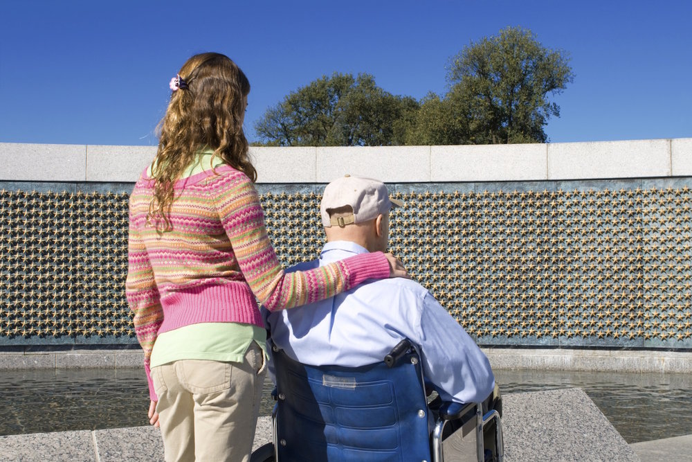 A girl with her arm around an elderly man in a wheelchair. They both look at a veterans memorial with hundreds of stars on it.