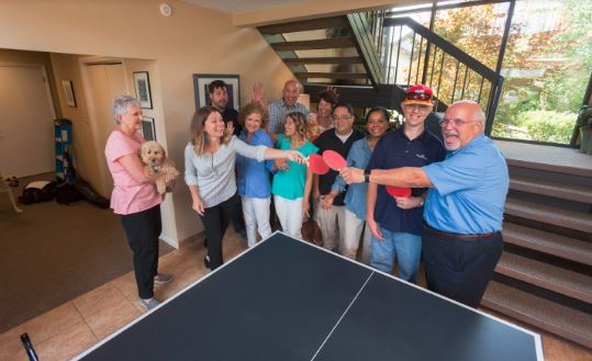 The  Simply Home staff gather around the ping-pong table for a group picture at the office.