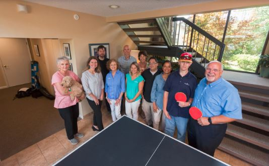 The  Simply Home staff gather around the ping-pong table in the  Simply Home offices.