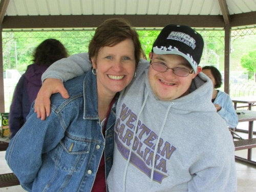 David (right) puts his arm around his mom Becky (left) and they both smile for a picture.
